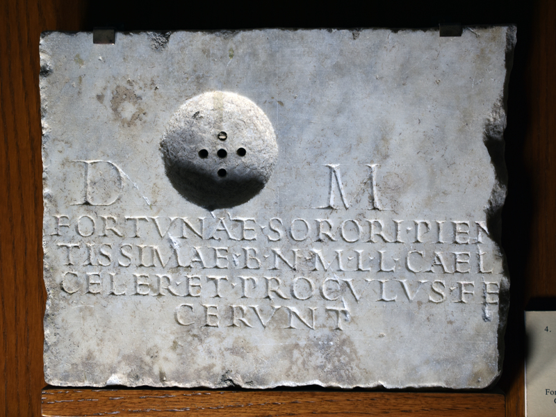 Plain plaque with pierced circular depression for pouring offerings into the cinerary urn (probably an olla)