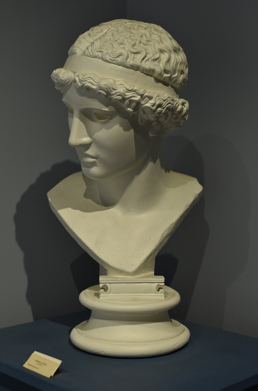 "The original acrolithic statue was created by Pheidias (ca. 440-435) and paid for by Athenians living on the island of Lemnos (hence, the ""Lemnian Athena""); the statue stood on the Acropolis in Athens. The Wilcox Collection has a plaster cast replica of one of the two existing Roman marble copies. The Roman copies, a head preserved in Museo Civico, Bologna, and a body that is shown in the Staatliche Museum, Dresden, were modeled after an original Greek bronze. Adolf Furtwängler reconstructed the statue in 1891. His reconstruction is in Dresden. There is also a well-preserved cast of the whole figure in Oxford, England. The association of the head and body has been disputed, and Athena is also missing her arms. It is presumed that she held either an owl or a helmet in her outstretched arms. The original sculpture was among the first of many famous works to come, including Athena Parthenos at Athens and the Zeus in the temple of Olympia. It was said by the ancient Pausanias that the Athena Lemnia is the most worth seeing of the works of Pheidias."