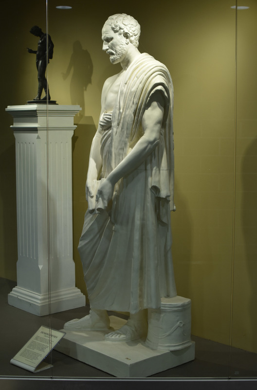 "Modern plaster replica of Roman marble copy of the Greek bronze original by the sculptor Polyeuktos, dating ca. 280 BCE. Perhaps the most well-known of the Greek orators, Demosthenes is said to have overcome his stuttering speech by speaking with pebbles in his mouth against the roar of the sea. A writer of speeches for the courts, Demosthenes was a passionate defender of his native Athens and in a series of speeches known as the ""Philippics"" he urged his fellow-citizens to withstand the advances of Philip of Macedon, father of Alexander the Great. Over 50 Roman copies of the work are known; the original of ours is in the Vatican Museums in Rome."
