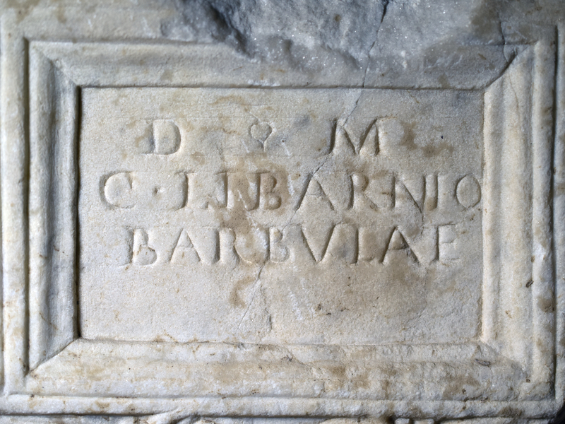 Small ash urn of white marble with inset plaque flanked by cornucopiae rising out of baskets; two antithetic griffins with curled tails {like hippocamps} below; faces at the corners.