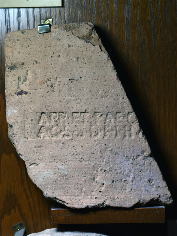 Speciality fragment of blunted triangular contour, blunted apex & contiguous side finished edges, broken edge joining sides edges rounded.In two rows in middle of fragment as pres in capital letters: APRETPATC/AGSSDEFI H for: