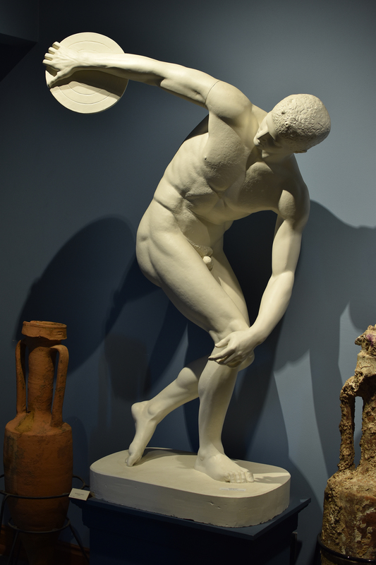 """Myron was a mid-5th century Greek sculptor who worked mainly with bronze and experimented with movement and the depiction of motion. Many ancient writers viewed Myron as transitional, between the Early and High classical periods, because he followed the path towards realism of the anatomy, hile avoiding the expression of emotion (Pedley 1993: 218). Myron had a reputation for sculpting figures caught in the instant of action, such as a runner on tiptoes or the Diskobolos (Boardman 1993: 95).  The Diskobolos was created about 450-440 B.C., and it completely represents the style of the Classical period. The style and purpose of classical art was an idealized treatment of the human body. The Diskobolos is the classical model of male beauty; he has a chiseled figure, perfect muscular form and is well-proportioned . In addition, classical sculpture had a psychological component as well. The discus thrower's face shows no strain, and the facial features are calm. lassical sculpture intended to portray noble simplicity and calm grandeur (Artoutthere, Classicism: accessed 11/1/01).  The Diskobolos of Myron has been described by Lucian,a 2nd century author, as """"an athlete stooping in the pose of one preparing to throw, turning towards the hand with the discus and gently bending the otherknee, as ready to rise and cast."""" This description is helpful to archaeologists because the original bronze no longer exists, and they are able to use this description as a method by which to identify copies of Myron's original (Pedley 1993: 218). The original was believed to have stood in a group with Athena on the Acropolis in Athens (Cavazzi, Sculpture of Greece: accessed 11/1/01). Currently, one can view copies of this sculpture in Rome at the Museo Nazionale delle Terme, the Musei Vaticani, Sala della Biga, the Louvre in Paris, as well as, a plaster cast in the Wilcox Collection in Lippincott Hall. The cast is composed of a copy of a marble head placed on a copy of a marble body-version o"""
